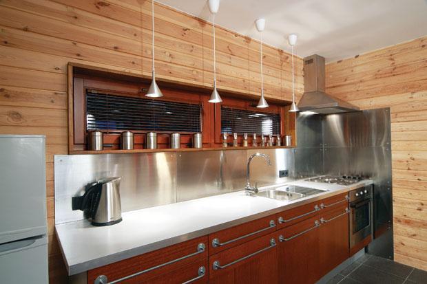 Деревянная обшивка стен делает помещение кухни более уютным и домашним