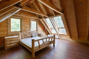 Интерьер спальни в деревянном доме в мансарде