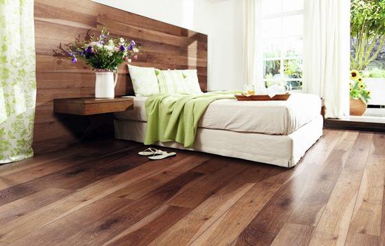 Как вариант — обшить ламинатом подходящим под тон пола стену у изголовья кровати