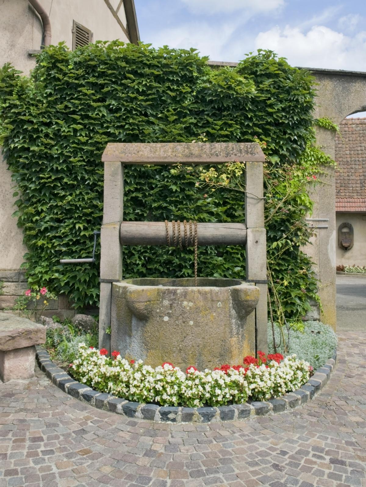 Старинный каменный колодец среди цветов