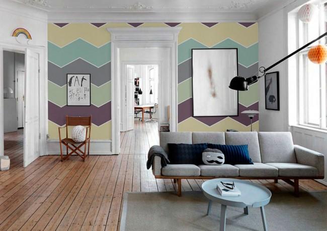 В комнате с высокими потолками разноцветные обои зигзагообразного рисунка